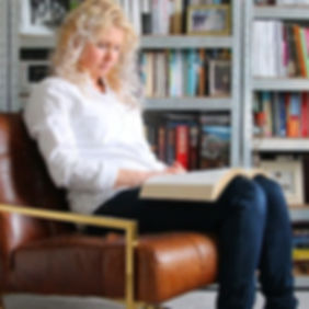 Woman sat in front of bookcases reading Bible