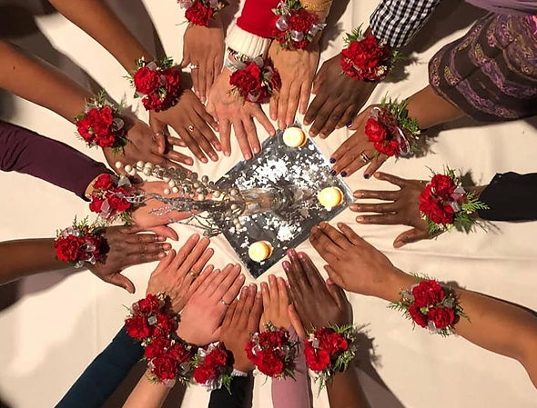 hands arranged in a circle around a plate with candles