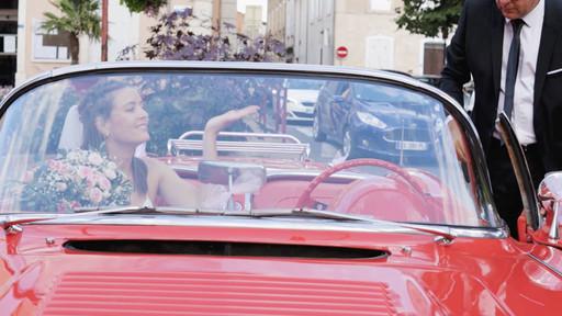 Sortie d'église de la mariée dans une voiture décapotable rouge et vintage