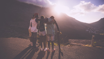 Group of friends standing on a mountain side overlooking a river.