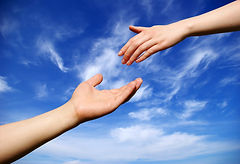 Hand reachin out to help another one against a blue sky.