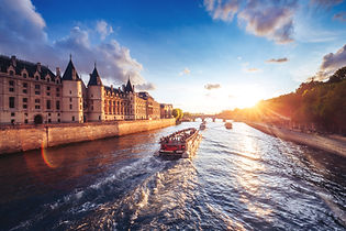 Dramatic sunset over river Seine in Paris, France, with Conciergerie and Pont Neuf. Colour