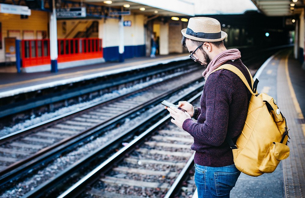 6 Different Ways to Type on Your Smartphone: man standing at a train track typing something on is smartphone.