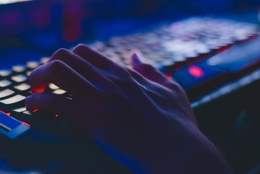 Iemands linkerhand op een mechanisch toetsenbord, met neonkleuren. Dit geeft het het gevoel van een gaming toetsenbord.
