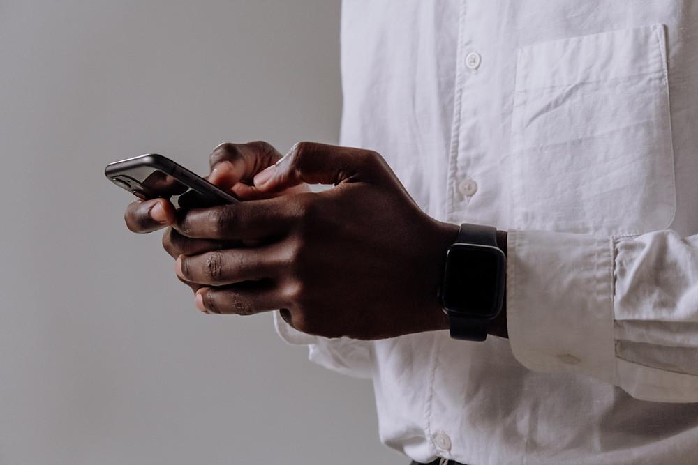 De smartphone: man met witte shirt die een zwarte iPhone vasthoudt met lichtgrijze achtergrond