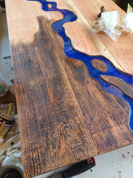 Applying finish to a river table.