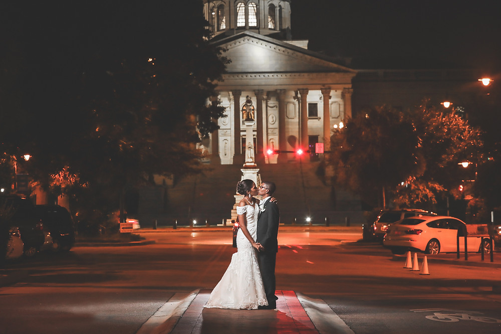 The bride and groom pose for a portrait in front of the SC State House