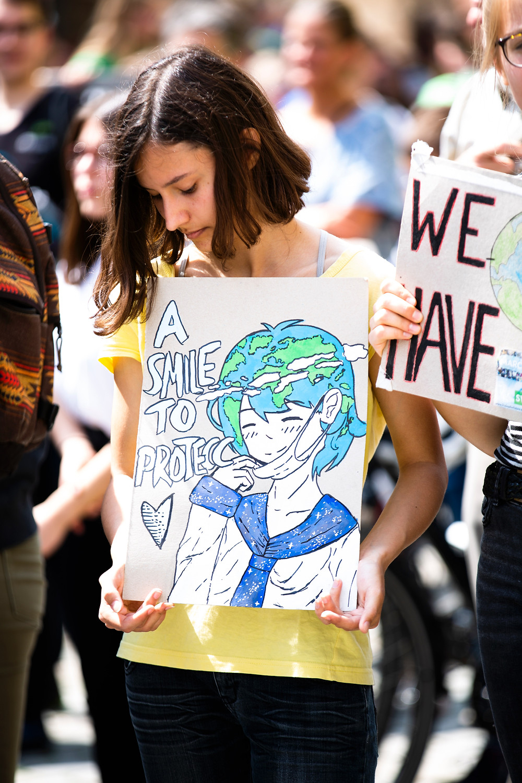 """Seorang perempuan ditengah keramaian, kemungkinan besar sebuah demonstrasi. Dia sedang memegang sebuah poster, yang terdapat gambar seorang perempuan dengan rambut seperti bumi. Di poster tersebut, juga terdapat tulisan: """"A Smile to Protecc"""", atau """"sebuah senyuman untuk melindungi""""."""