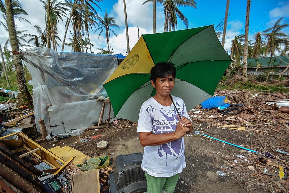 Seorang perempuan yang memegang sebuah payung. Dibelakangnya, terdapat banyak sampah.