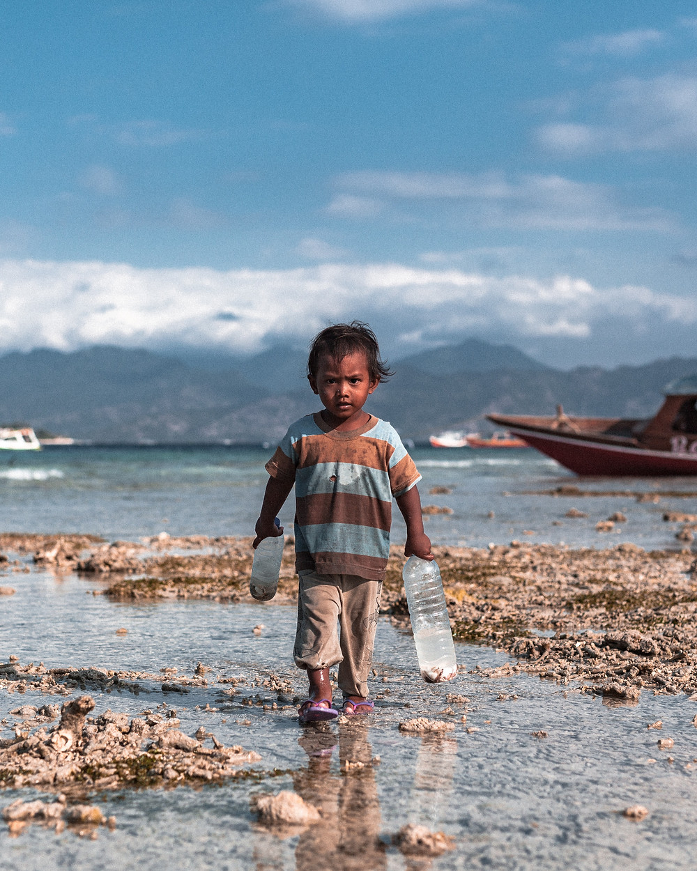 Seorang anak kecil di pantai yang sedang memegang dua botol besar (yang kemungkinan besar adalah sampah)