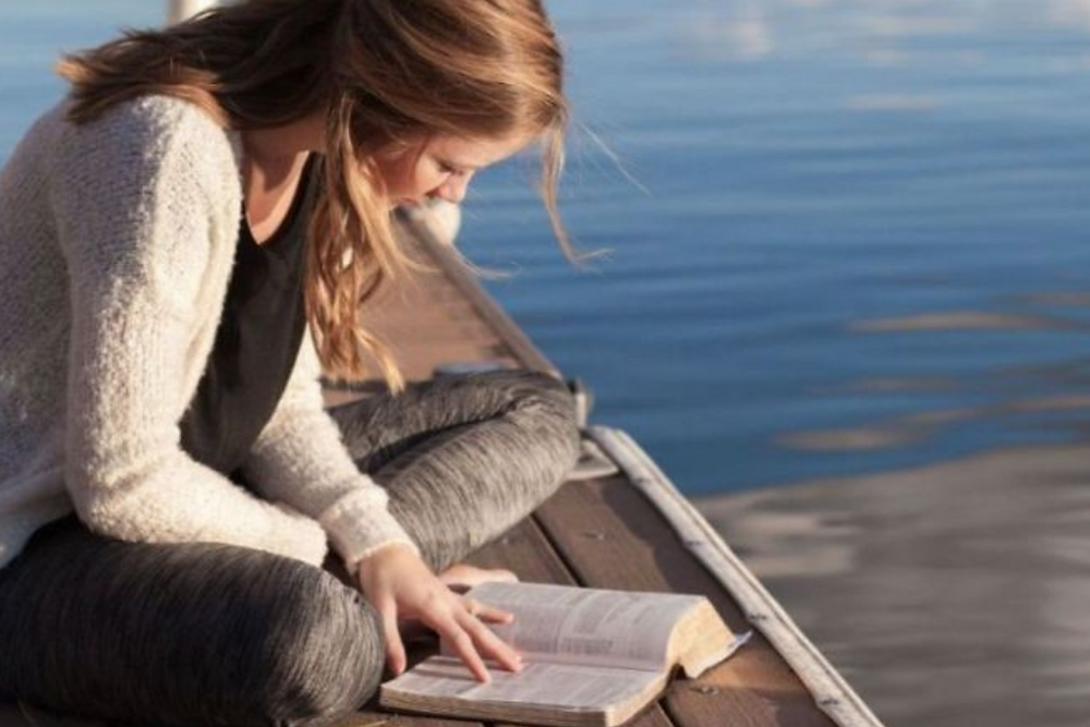 Image of woman reading a book on a dock with water in the background.