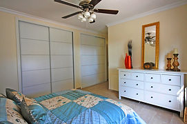 Large bedroom with king size bed, huge wardrobe space and dressing table. View of the sea, pool and gardens