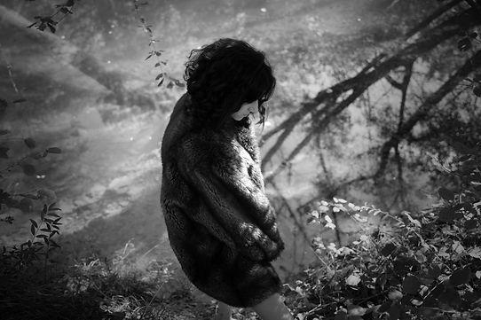 Studio-mune femme appuyée sur un arbre eau turquoise gouffre cajarc nature forêt féminine  noir et banc ombres et lumières ombre et lumière regard noir fourrure