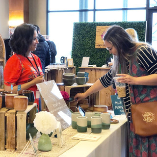 shopper viewing clay products with vendor at boerne handmade market