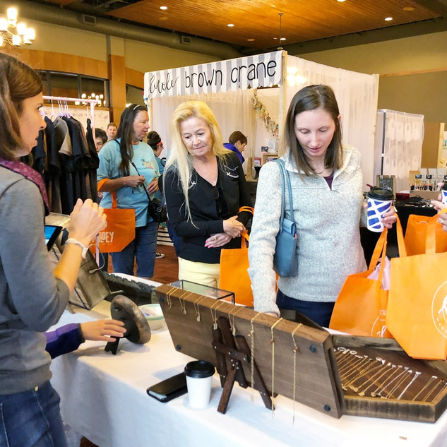 shoppers viewing jewelry products with vendor at boerne handmade market