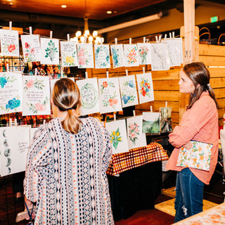 shoppers viewing art prints home decor at boerne handmade market