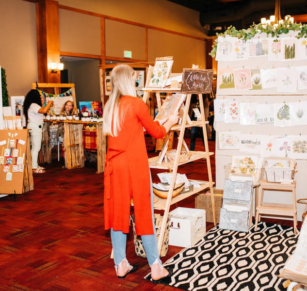 shoppers viewing art prints and home decor at boerne handmade market
