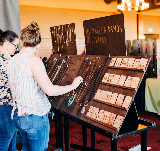 shoppers view jewelry from rebecca ramos jewelry at boerne handmade market