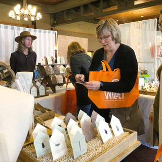 shopper viewing jewelry products with vendor at boerne handmade market