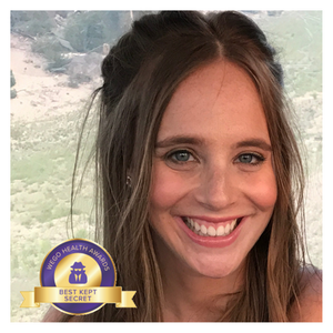 "Alyssa, a white woman with fair skin, freckles, and blue eyes, smiles into the camera. Her hair is pulled back. Behind her is a mountainous landscape. A purple and gold WeGo Health Award badge sits in the bottom left corner of the frame, with the title ""Best Kept Secret""."