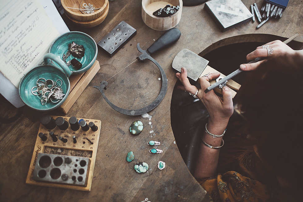 Top-down photo of silversmith creating jewellery at a workbench
