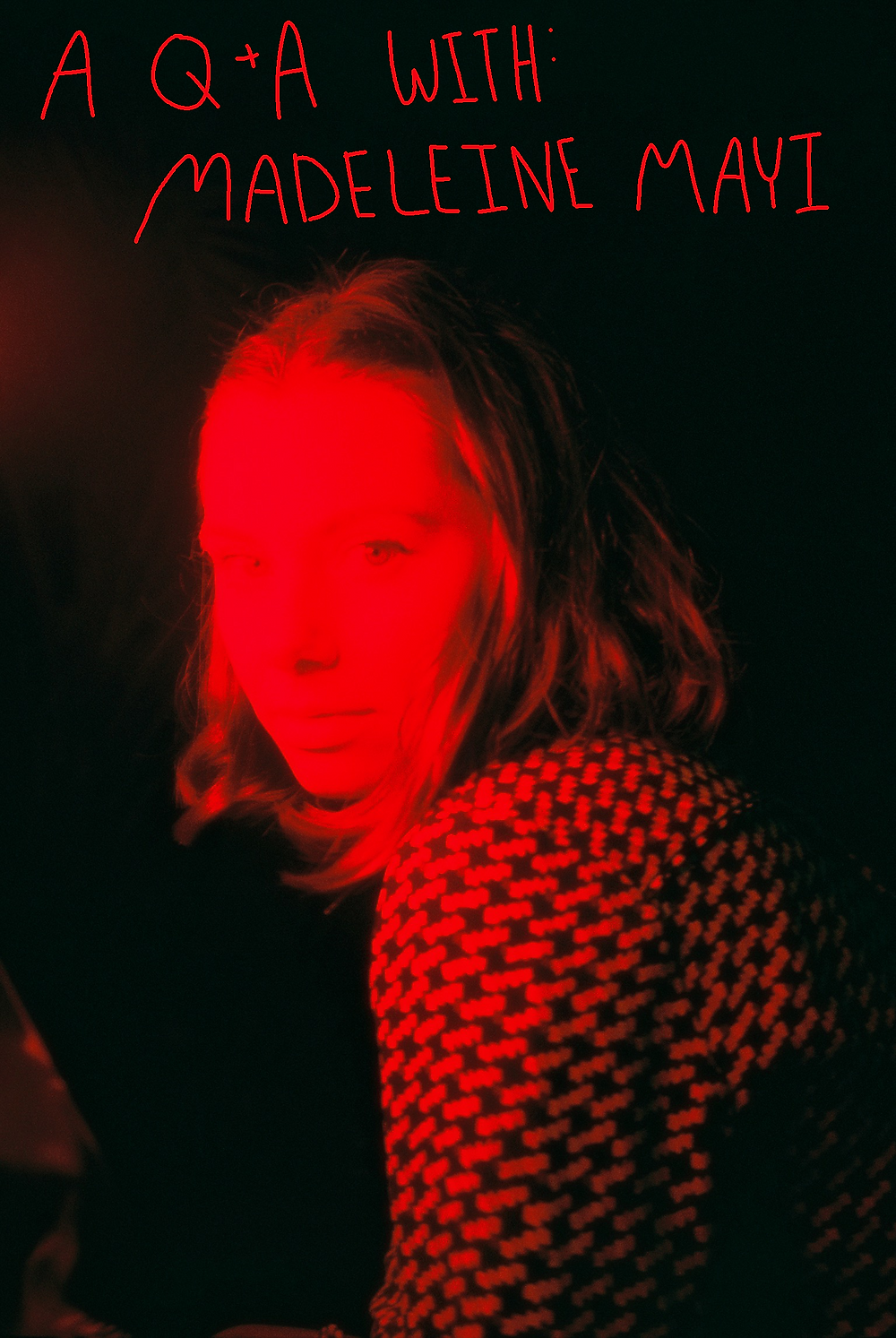 Madeleine Mayi is looking over her shoulder at the camera, under red light. The background is black. Hand-drawn red text reads: A Q&A with Madeleine Mayi.
