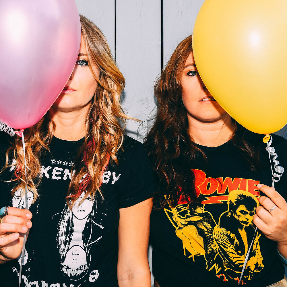 "A photo of Brianna Sage and Carrie Welling, who comprise Sugar Fitz, and it is the single cover for their song ""Skin Sparks."" Wearing a Bowie shirt and a Dead Kennedy shirt, respectively, both women are holding brightly colored balloons."