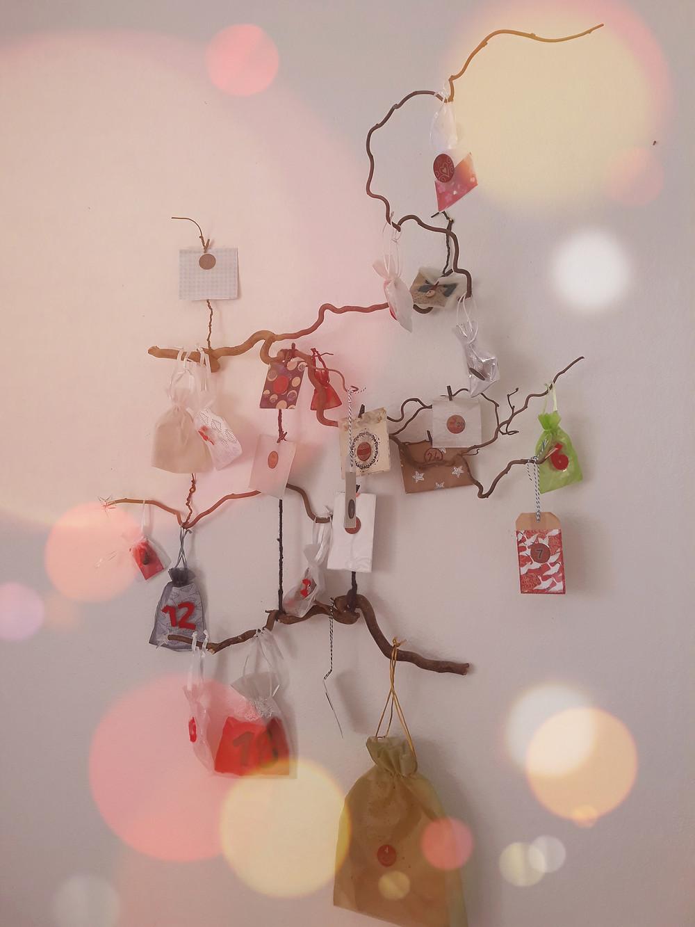 de jolies branches, des sachets en tulle, feutrine, ou papier, des rubans délicats et chocolats et autres sucres d'orge suspendus au mur pour la chasse aux numéros magiques