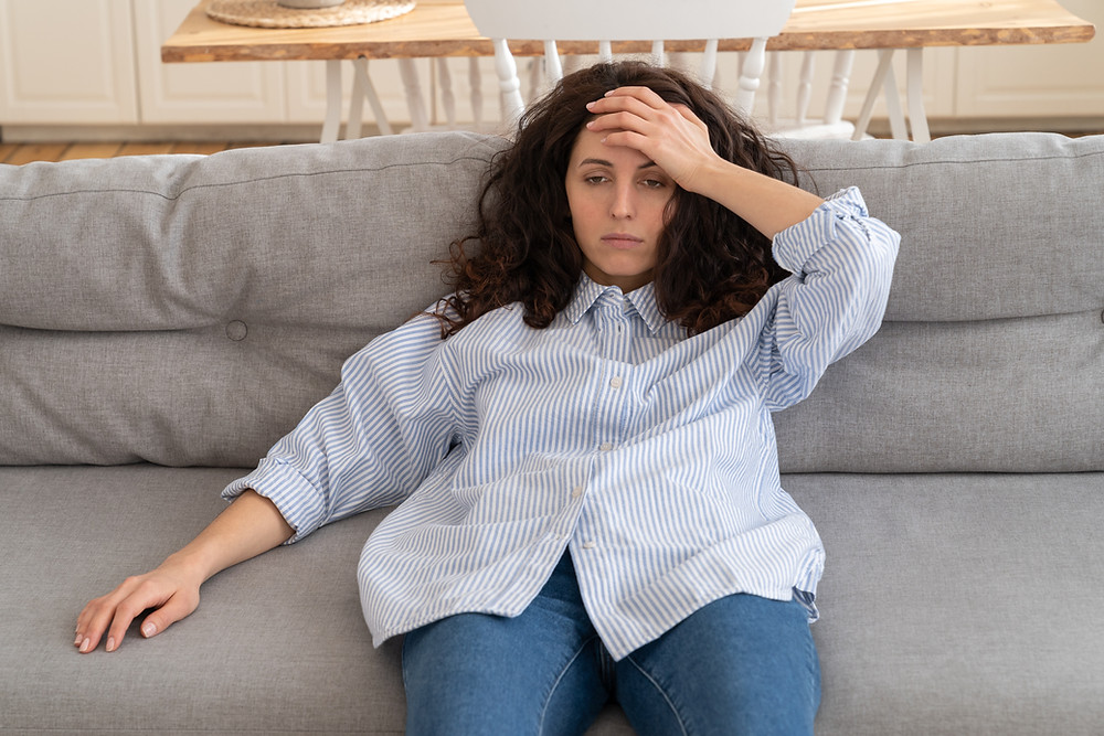 woman on sofa looking overwhelmed