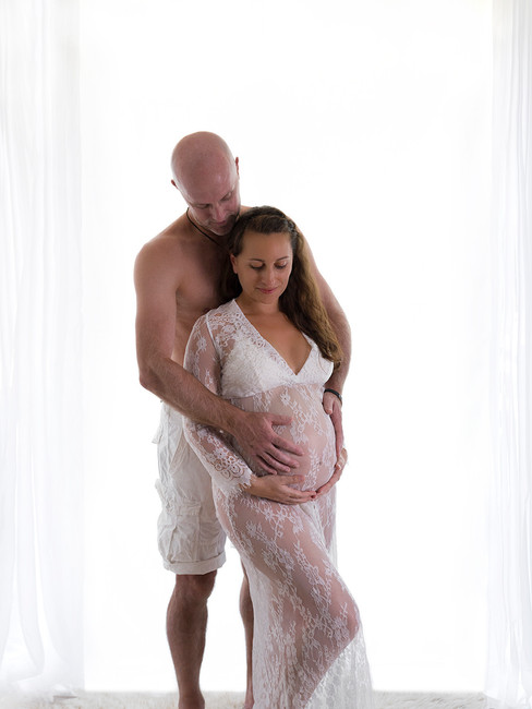 Pregnant couple in front of window
