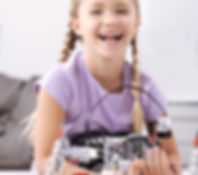 Smiling girl creating electronic robot a