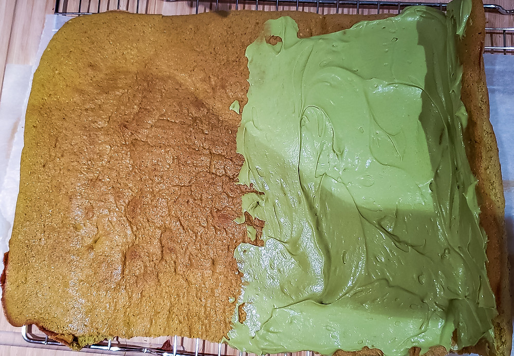 spreading matcha green icing on cake