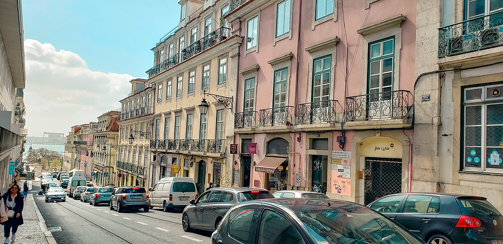 lisbon pink yellow buildings car walking