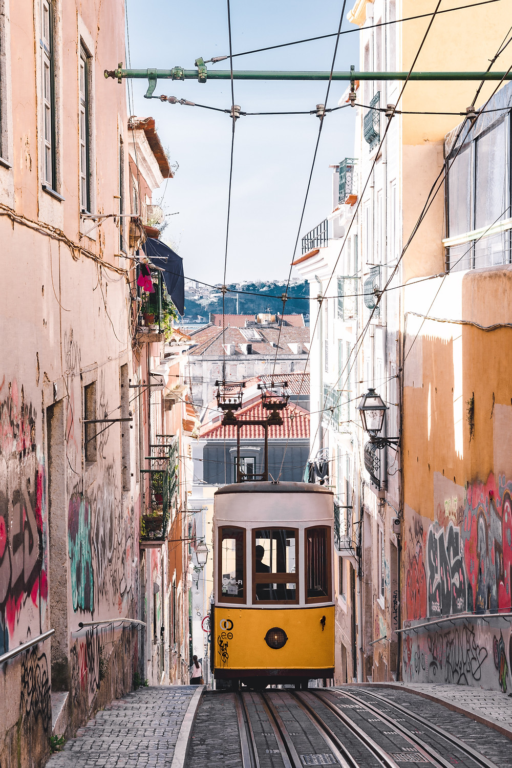 yellow trolley lisbon cobblestone road