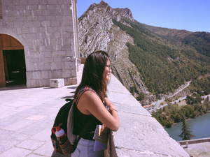 Girl looking out from a castle walk with a small mountain in the background