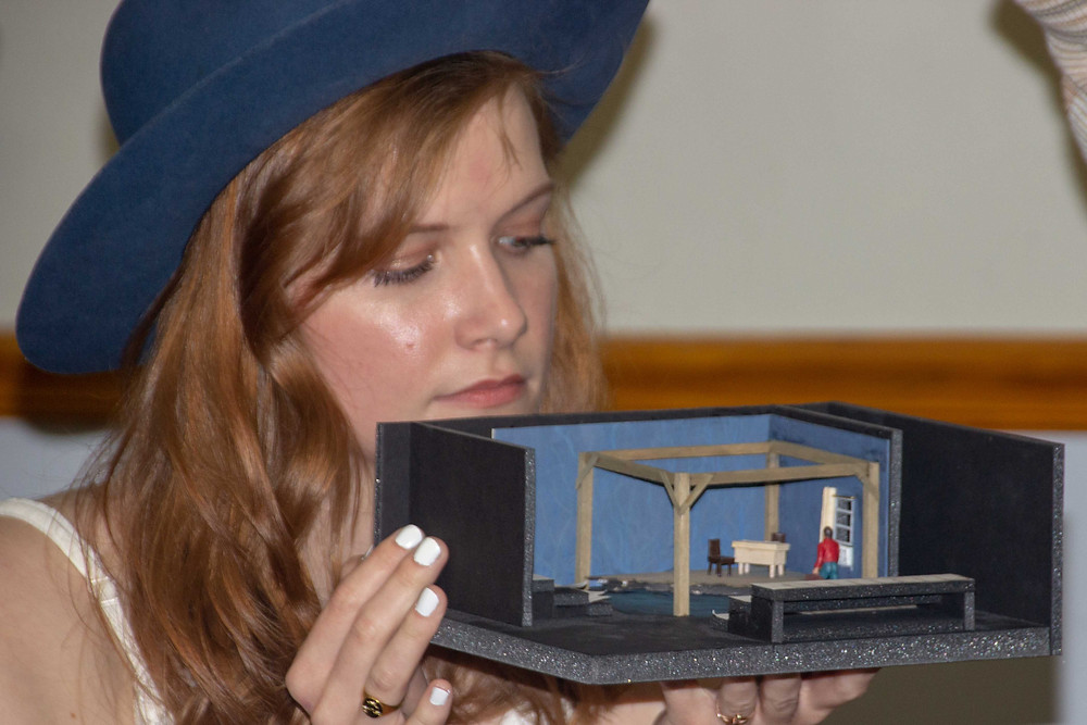 A white woman with long hair and a blue wide brimmed hat holds a model of a theatrical scenic design.