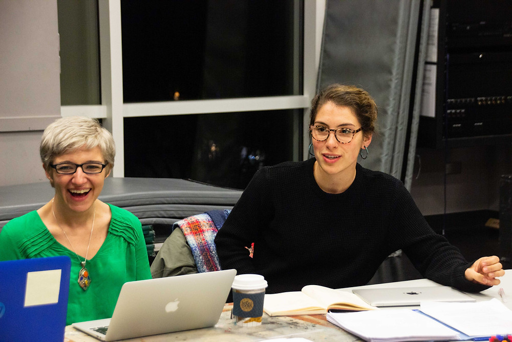 Two women sit at a table. One is laughing and the other is poised to say something. They have scripts, notes, a laptop, and coffee in front of them on the table.