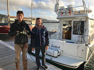 Two crew members next to a yacht