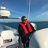 Man with a red life preserver on a boat