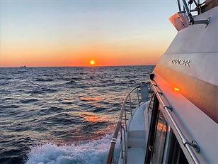 A boat at sea at sunset