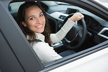 Smiling woman in the drivers seat in her
