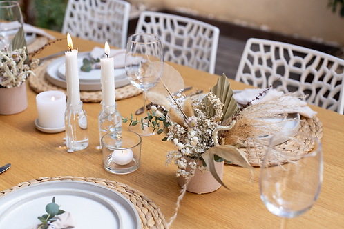 dried flowers bouquet inside white minimalist ceramic put and dust pink candles as dinning table decor