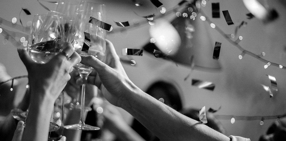 Black and white photo of hands raising wine glasses, confetti falling in background