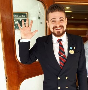 Nathan Cassar waving hello and smiling on the gangway of a cruise ship