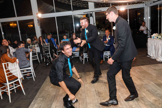 Nathan Cassar: Master of Ceremonies laughs with two others on the dancefloor during the garter toss
