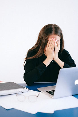 Woman stressing over a laptop, hands in head at desk