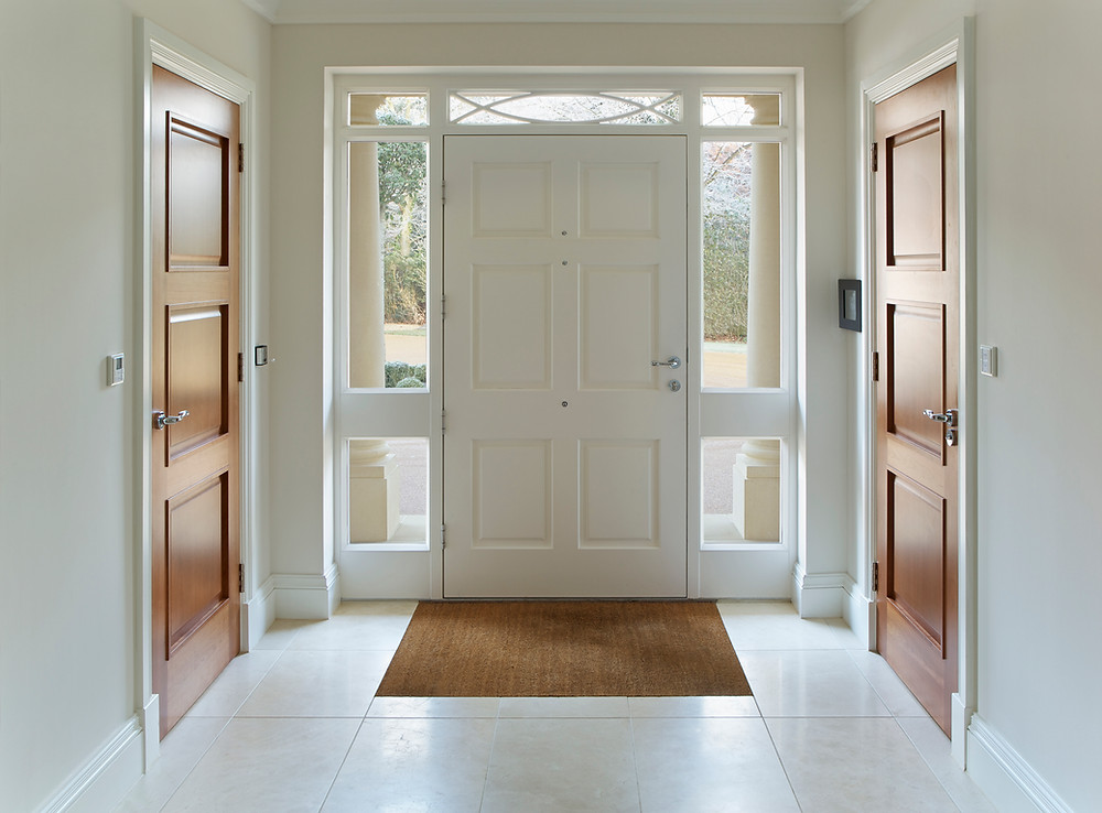 White entryway into house with large door and windows