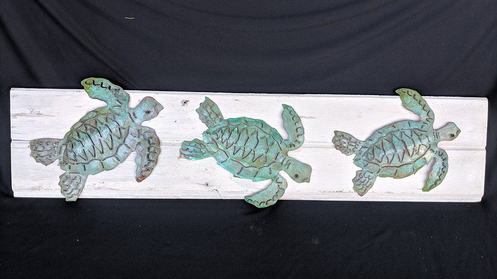Hammered copper sea turtles on vintage shiplap.
