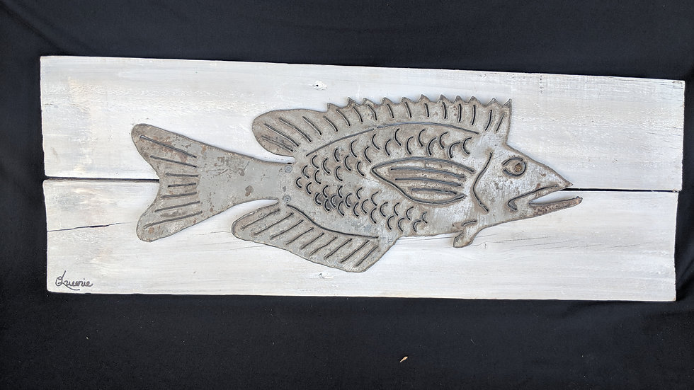 Fish in vintage metal on wood.
