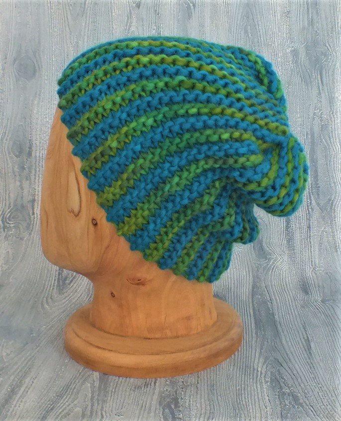 Hand-knitted beanie on wooden display head